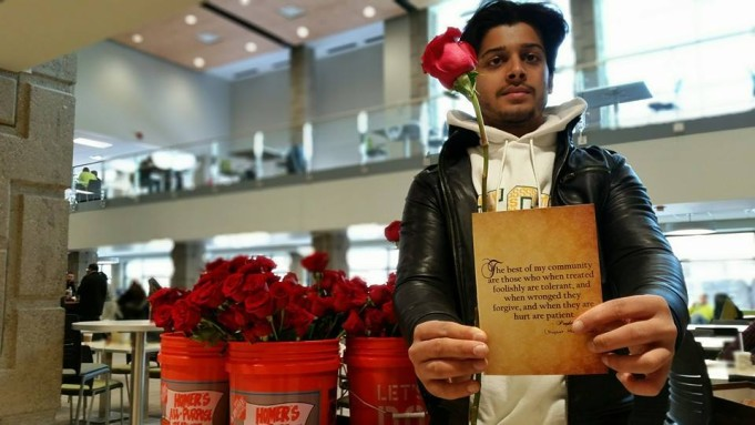 Saqib gives roses out at Wayne State. Photo Credit: Jessica Archer