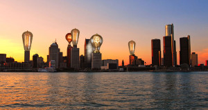 Photo illustration of lightbulbs plugged into the Detroit skyline.