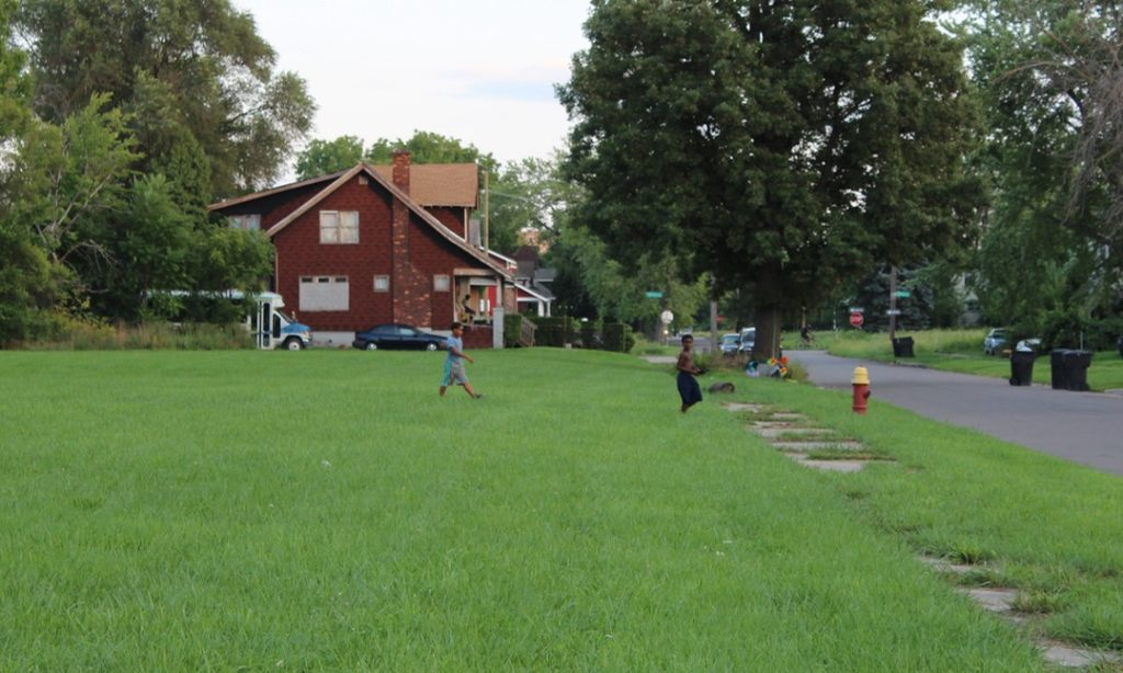 Children cross a field to play on Dickerson street in Detroit. Daily Detroit photo.