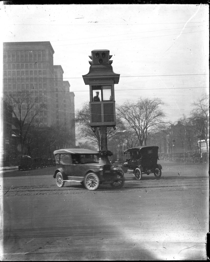 View of police officer standing in traffic tower ; two automobiles circle the tower.Courtesy of the Burton Historical Collection, Detroit Public Library.