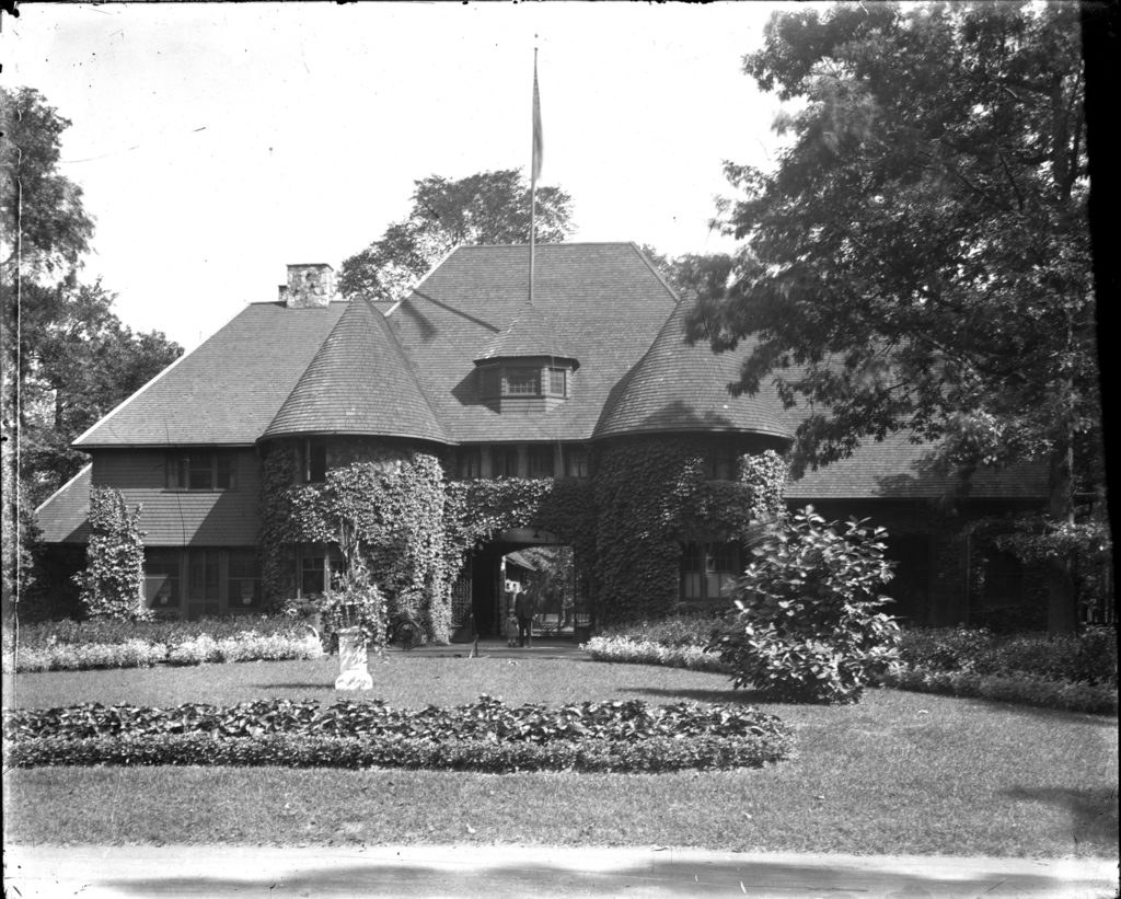 View of police station on Belle Isle; ivy-covered Shingle style building with turrets; man and small child stand in rounded arch entrance. Courtesy of the Burton Historical Collection, Detroit Public Library.