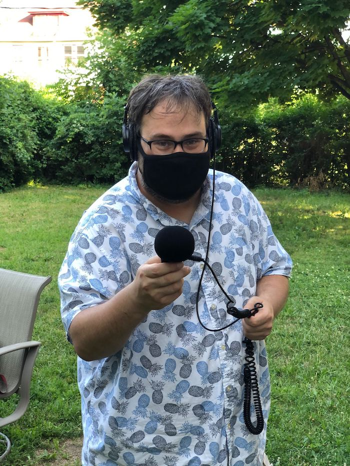 Jer wearing a mask and headphones while holding an audio recorder