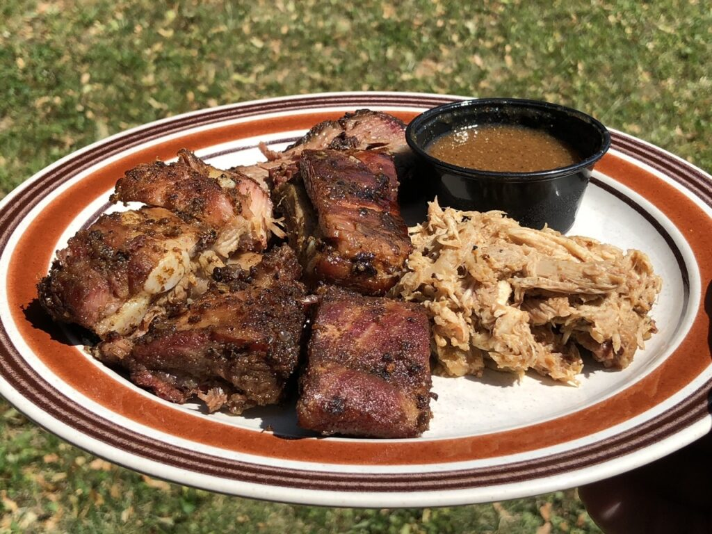 Plate of rib tips, brisket, pulled chicken, and barbecue sauce