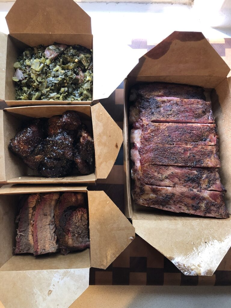 Containers of ribs, collard greens, burnt ends, and brisket