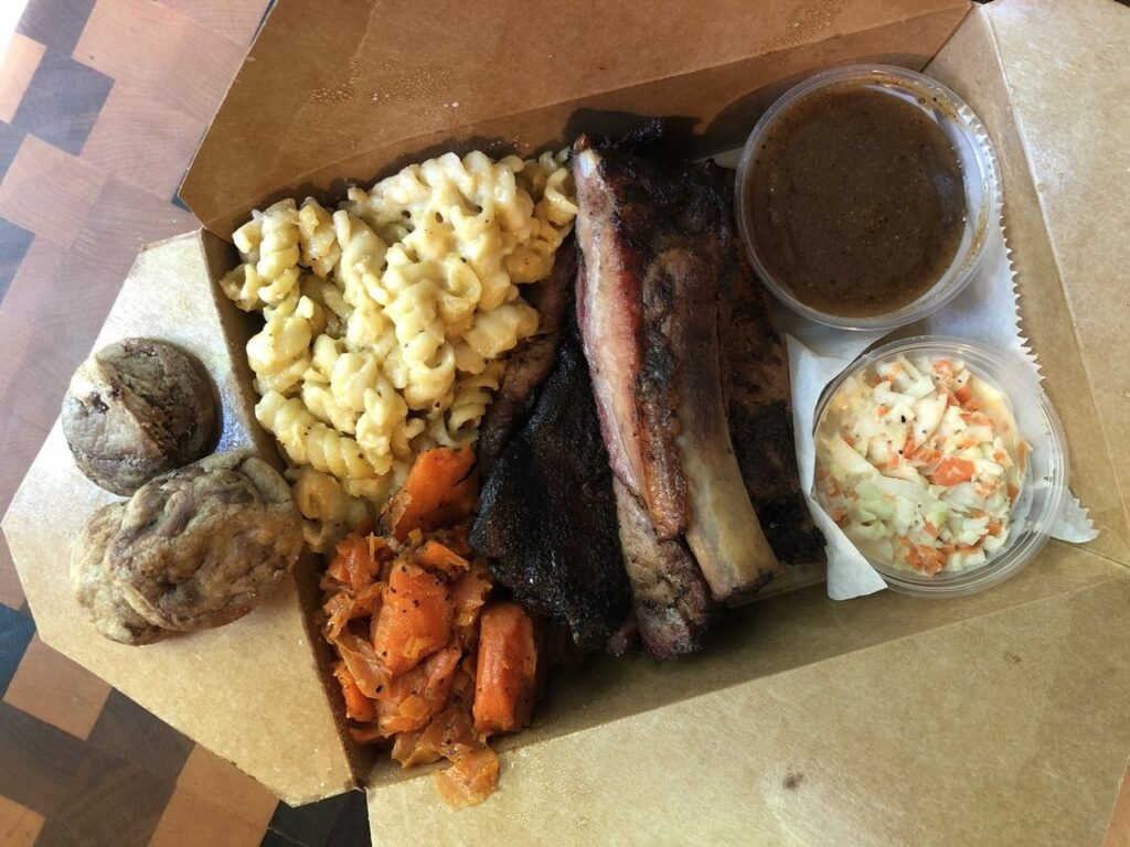 Container of ribs, macaroni and cheese, carrots, coleslaw, barbecue sauce, and chocolate chip cookies