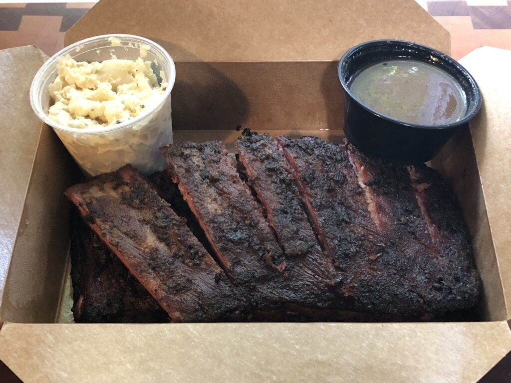 Container of ribs with potato salad and barbecue sauce